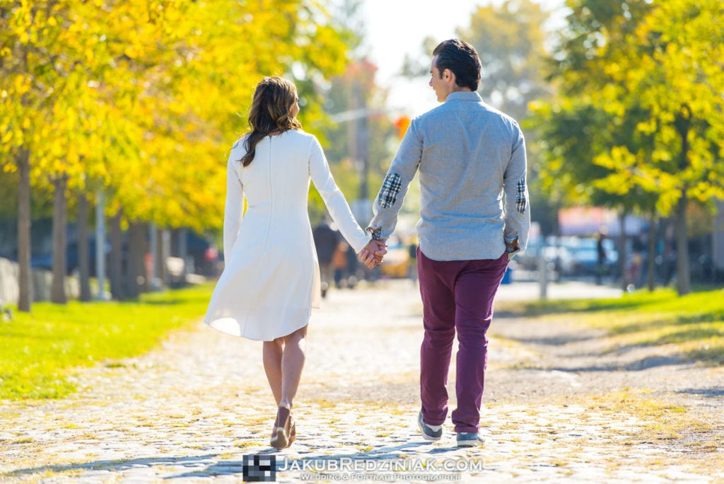 couple engagement session in east river state park in new york city holding hands on cobblestone with yellow trees walking from the back