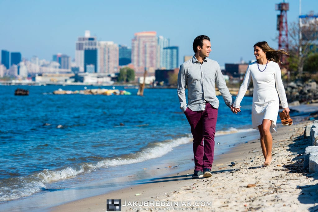 Couple Engagement Session by the East River in Brooklyn, NY holding hands walking on sand beach with nyc skyline