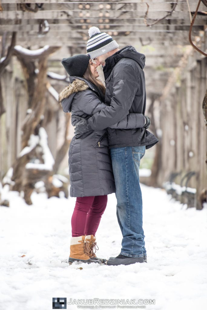 couple posing in the snow in central park for engagement session in new york city