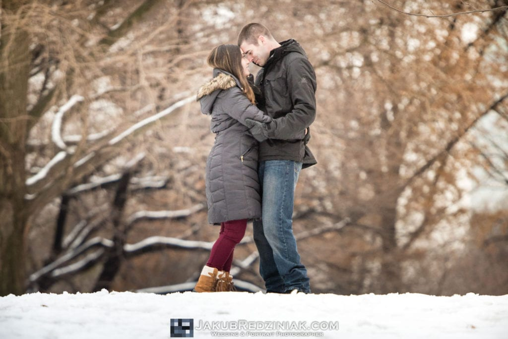 couple posing in engagement session together holding each other on a snow hill in central park in new york city in winter