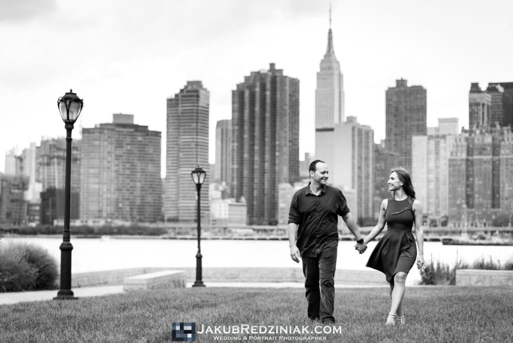 couple engagement session in gantry plaza state park in long island city new york city walking on  grass with city skyline holding hands