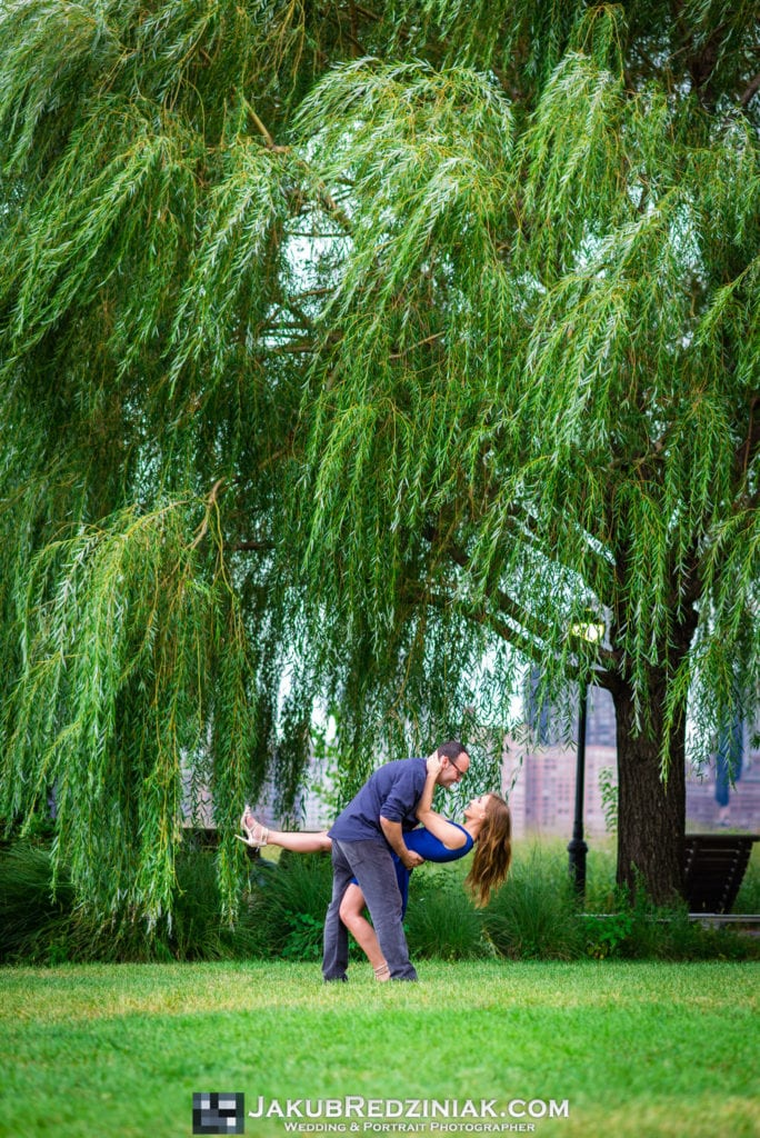couple dancing under weeping willow in gantry plaza state park in long island city new york man dipping girl engagement session