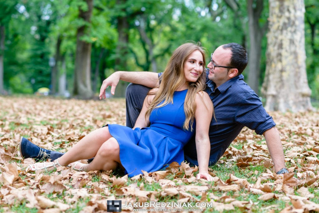 couple engagement session in central park on a fall autumn day with orange leaves sitting on grass and leaves