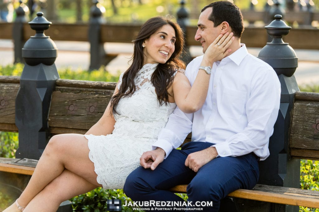 engagement session couple sitting on bench in central park