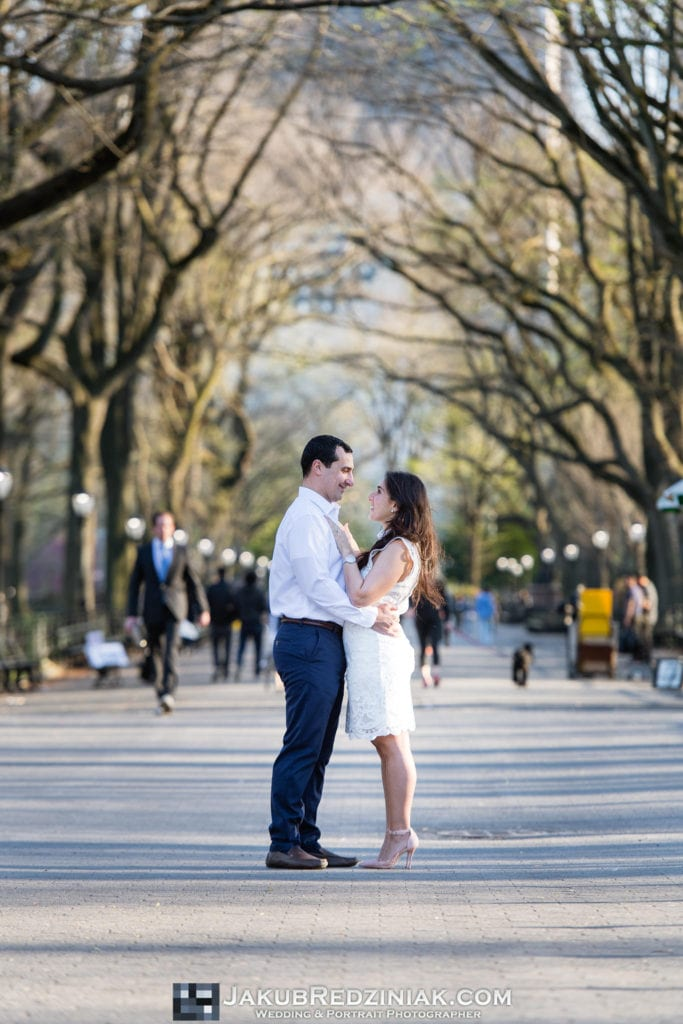 engagement session couple in central park standing in center with the mall