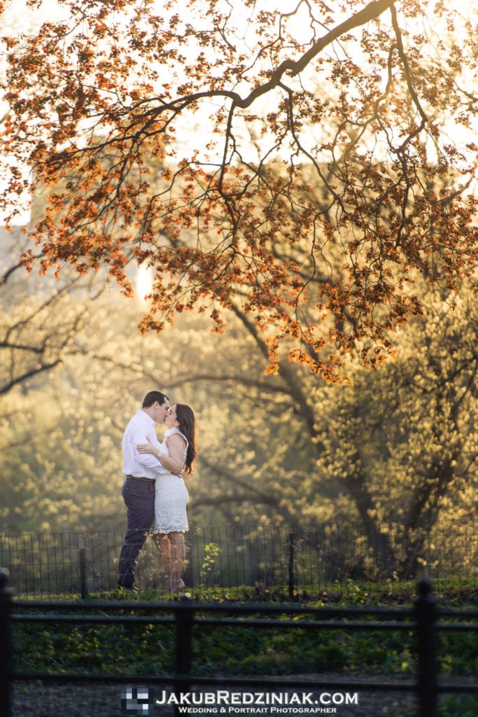 engagement session couple in central park standing under tree at sunset with orange leaves