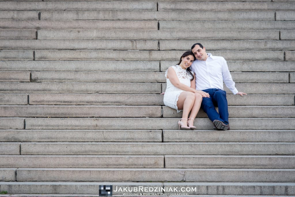 engagement session couple in central park sitting on steps at bethesda terrace