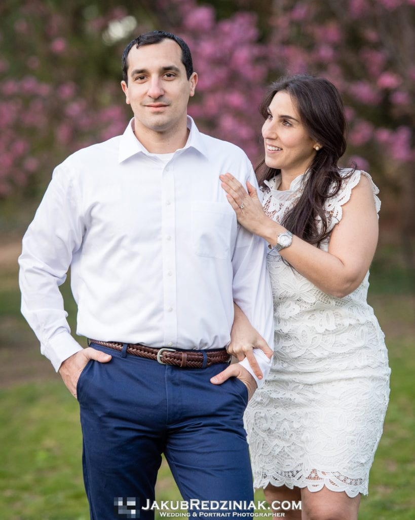 engagement session couple in central park standing under pink tree in spring
