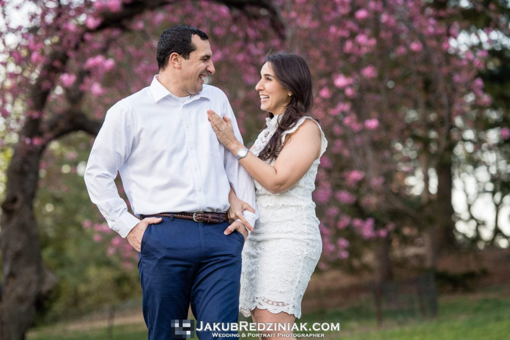 engagement session couple in central park standing under pink tree in spring laughing