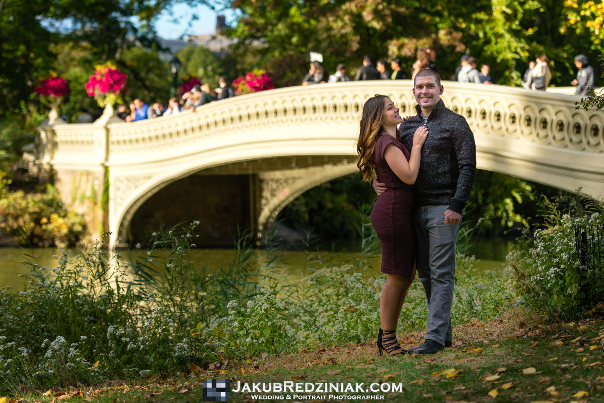 couple engagement session in front of bow bridge in central park new york city