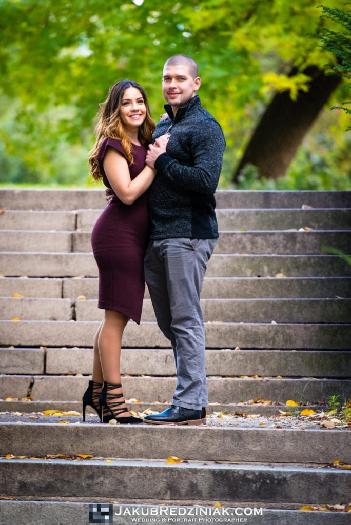 couple standing on steps for engagement session in central park new york city close to bethesda terrace