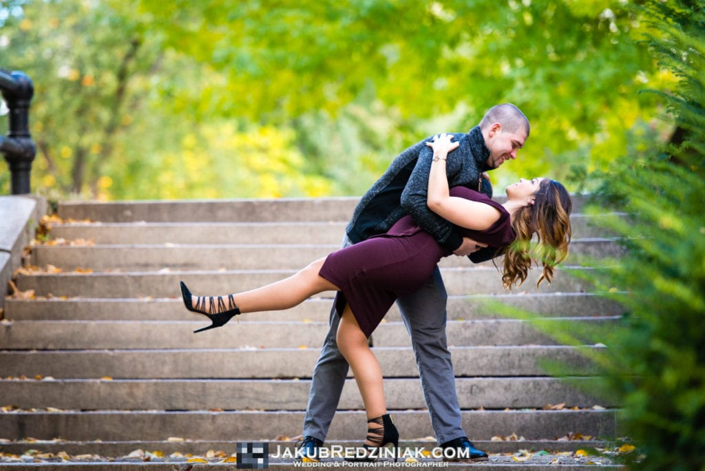 couple dancing on stairs for engagement session in central park new york city