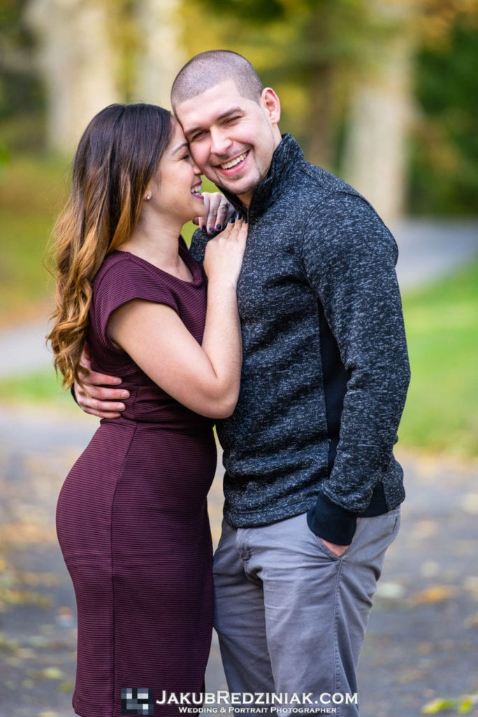 couple posing in fall yellow orange colors for engagement session in central park new york city close to bethesda terrace