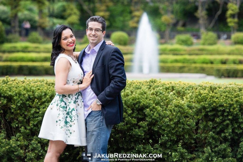 Couple posing in Conservatory Gardens Central Park in New York City for engagement session with fountain in the background