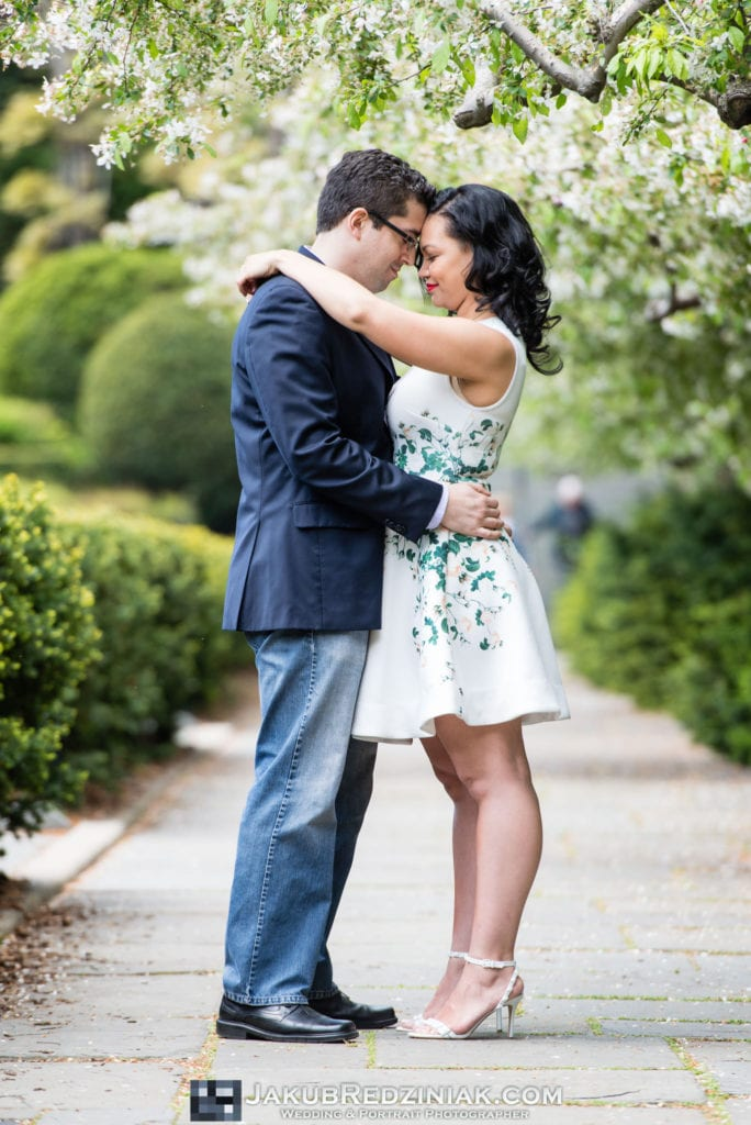 Couple posing in Conservatory Gardens Central Park in New York City for engagement session with spring blooming white flower trees