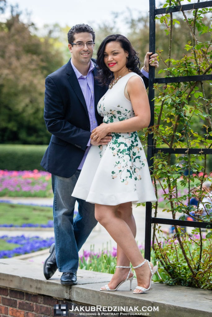 Couple posing in Conservatory Gardens Central Park in New York City for engagement session under arch and colorful tulips in the background