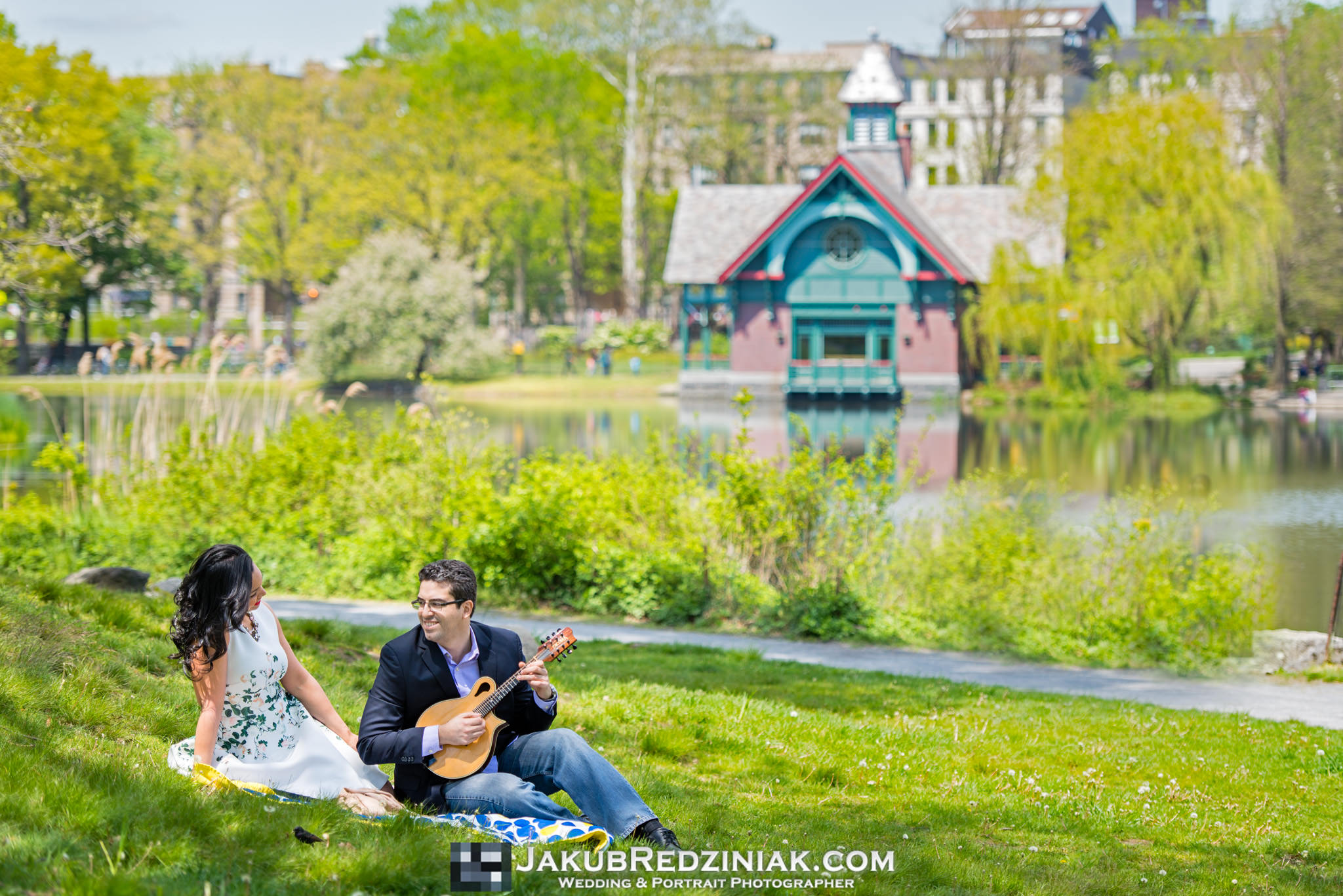 Couple posing on a picnic blanket with a guitar in Central Park in New York City for engagement session by boathouse