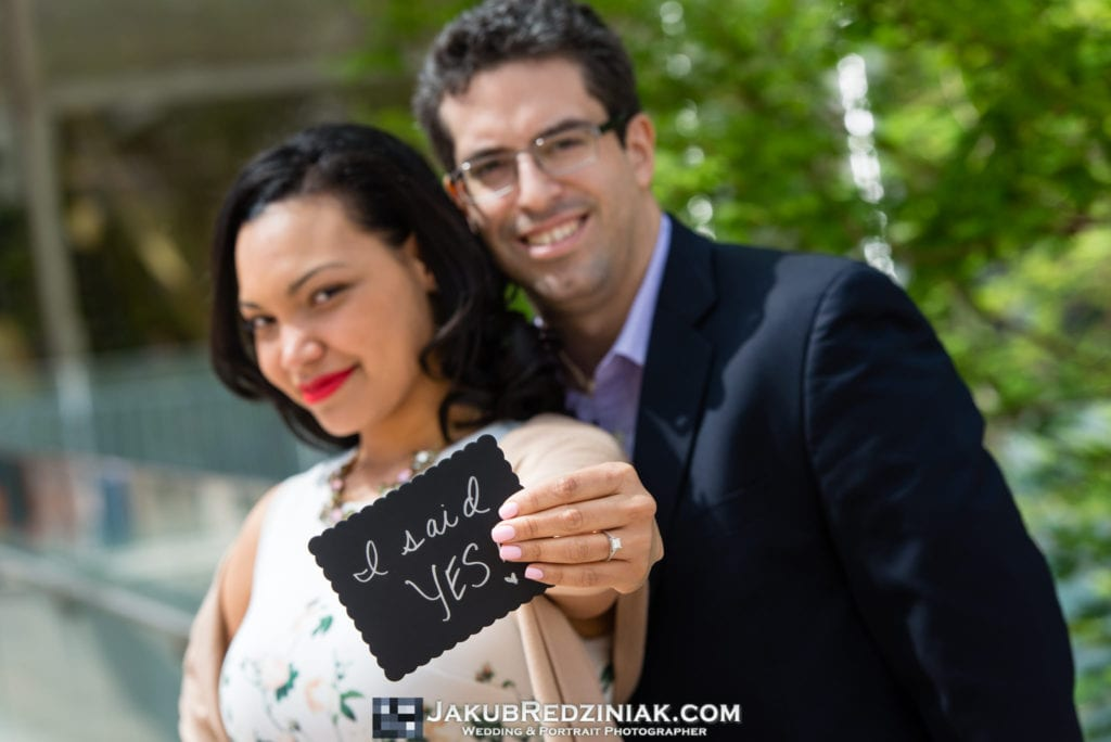 couple holding creative sign i said yes at engagement session after proposal