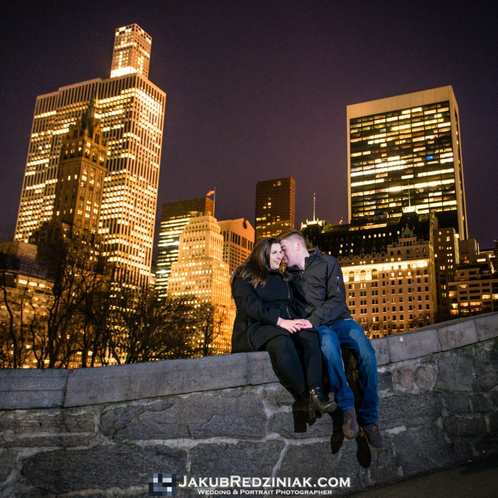 couple sittin on gapstow bridge in central park for night time engagement session with city lights in background by plaza hotel in new york city