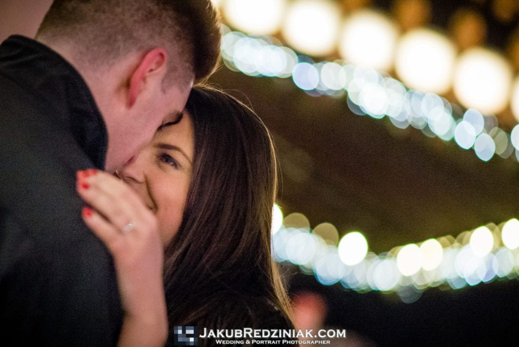 closeup of couple at night time engagement session in new york city at christmas time withi engagement ring