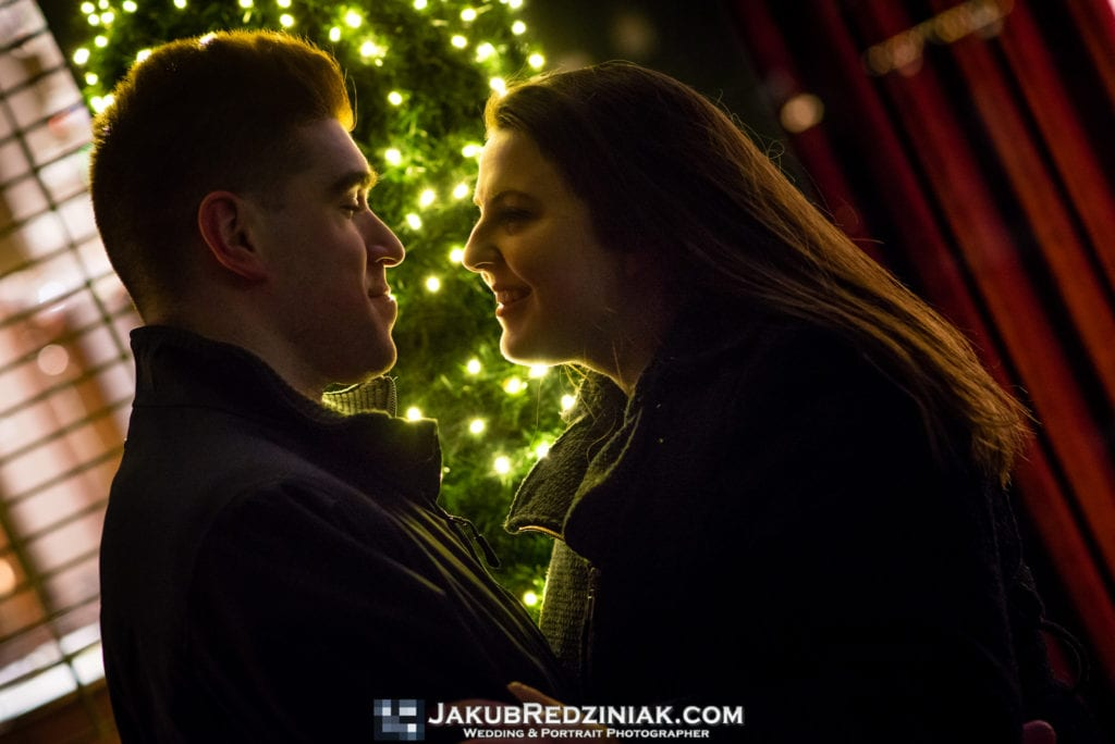 couple standing happy with Christmas tree and lights in background for night time engagement session outside of plaza hotel in new york city