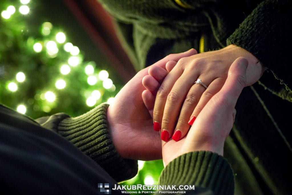 close up of engagement ring and hands of couple with christmas tree lights in background for winter engagement session in manhattan new york city