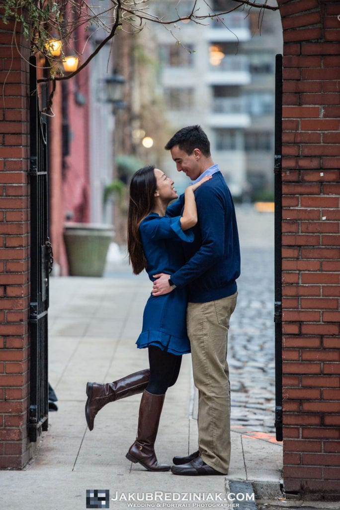 couple standing under arch in washington mews by nyu in new york city for engagement session after proposal