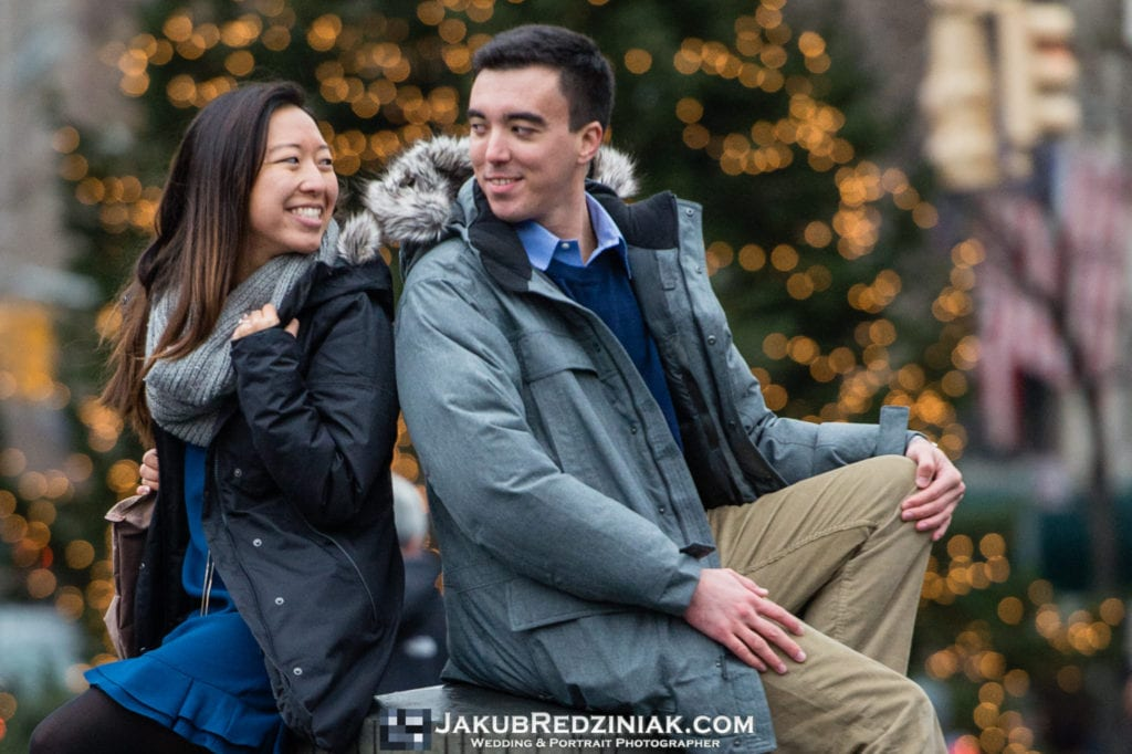 couple sitting in washington square park in nyc back to back creative pose with christmas tree
