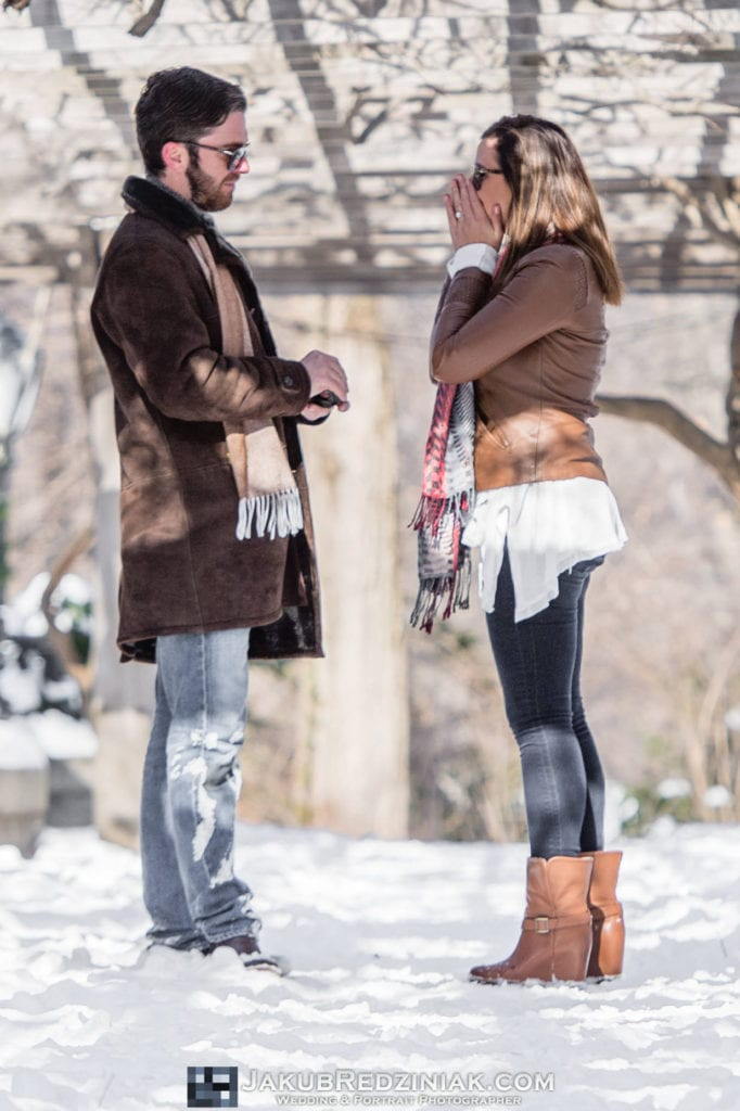 man proposing to girl in the snow in central park new york city