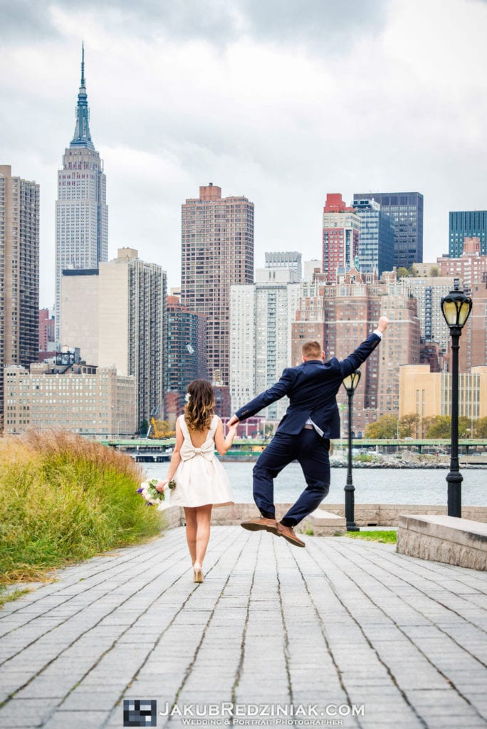Elopement photo session in new york city at gantry plaza state park in long island city by the east river with couple creative photo groom jumping holding hands with bride and nyc skyline