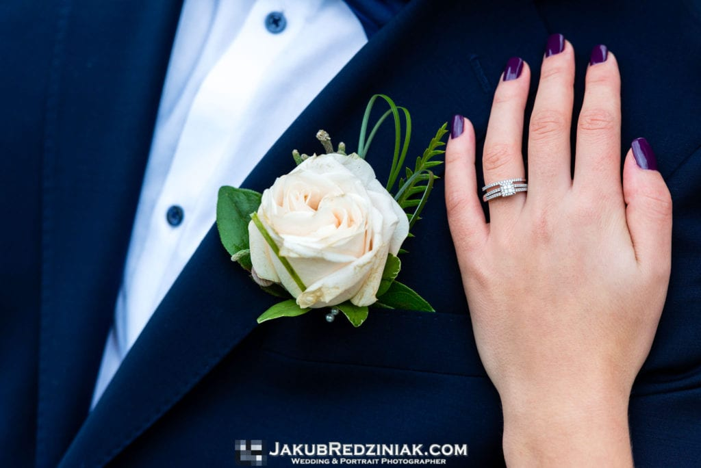 close up of engagement and wedding ring on groom lapel and blazer with flower