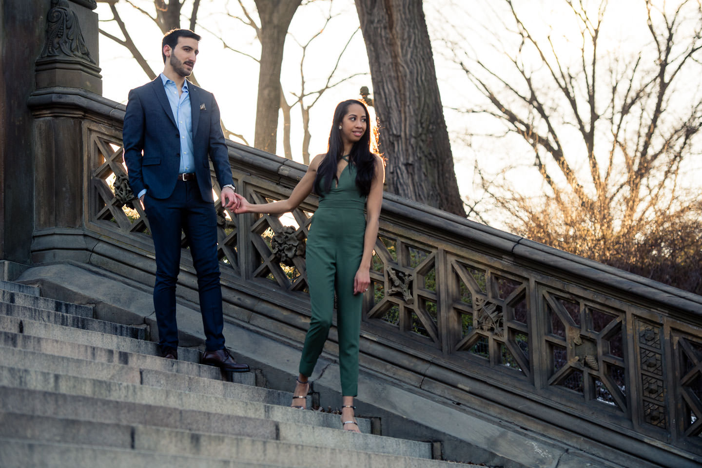 couple walking down steps by bethesda terrace in central park for their engagement session