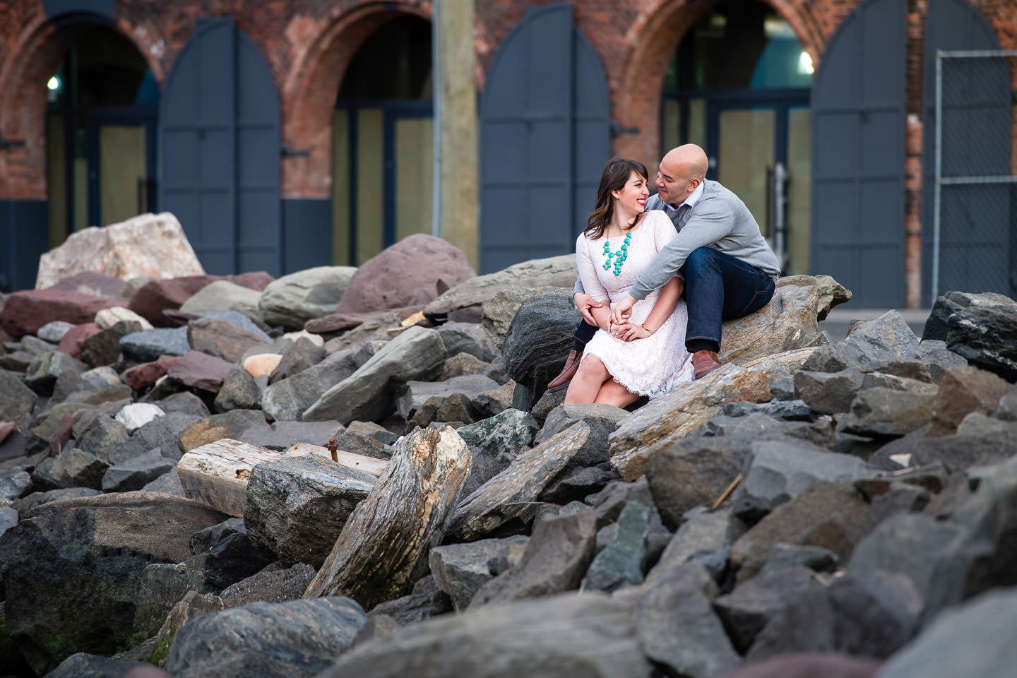 couple sitting on rocks kissing in brooklyn bridge park in dumbo for engagement session