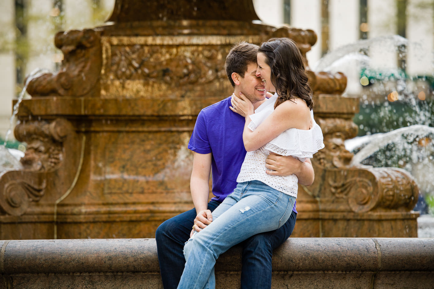 couple sitting on fountain in bryant park kissing and laughing