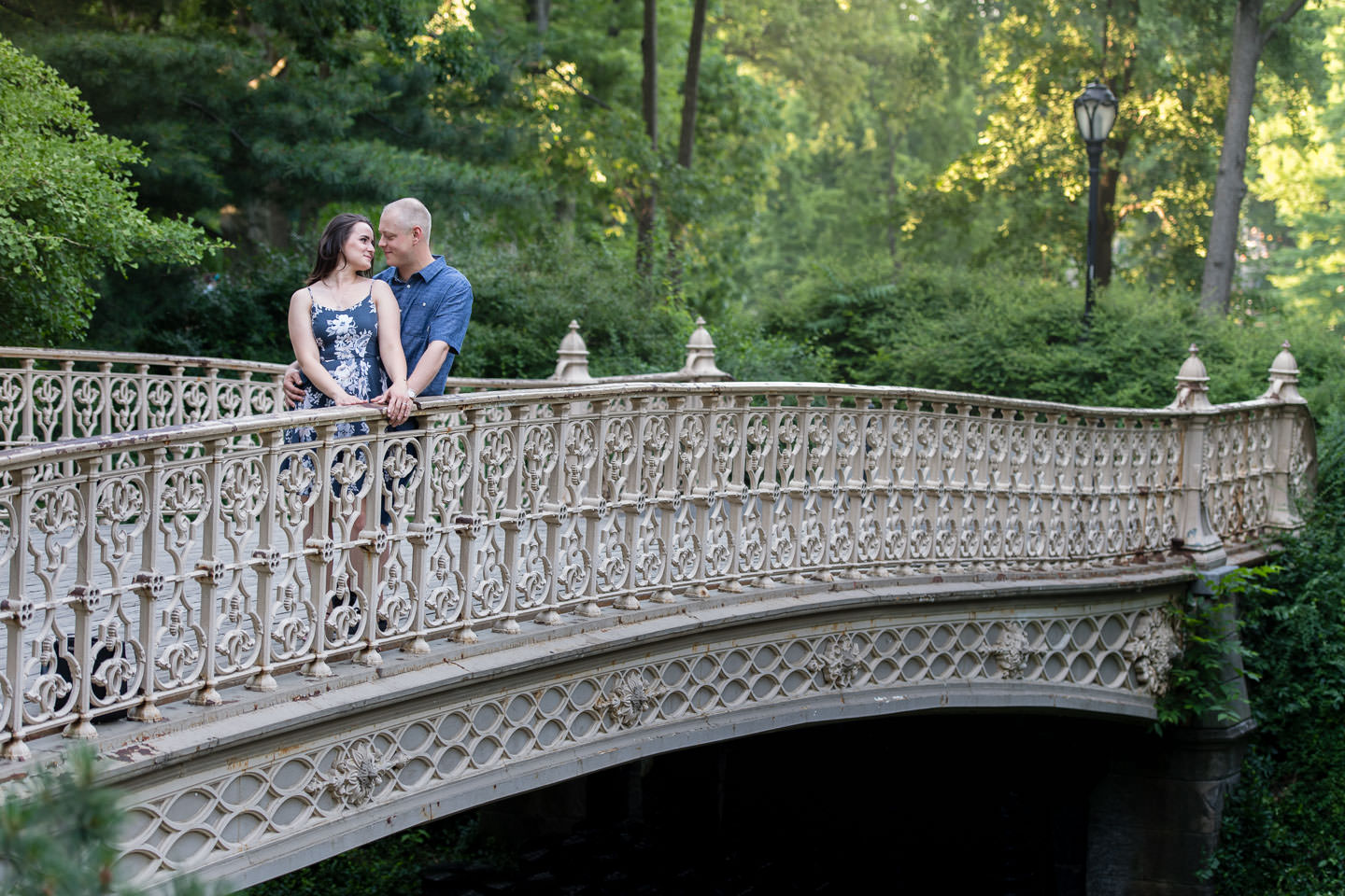 couple standing on bridge in central park for their engagement session