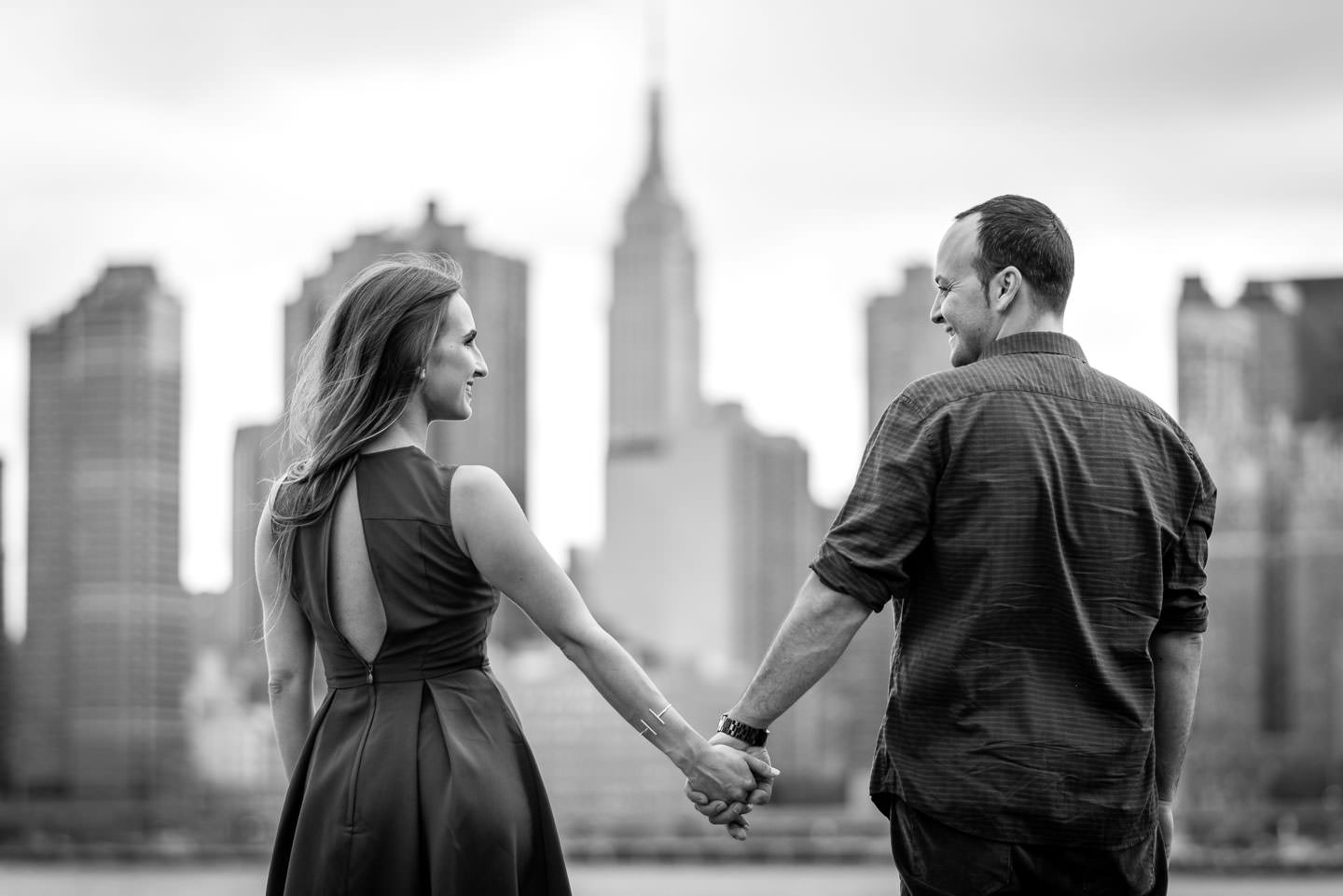 couple with empire state building in background at gantry plaza state park in long island city new york for engagement session