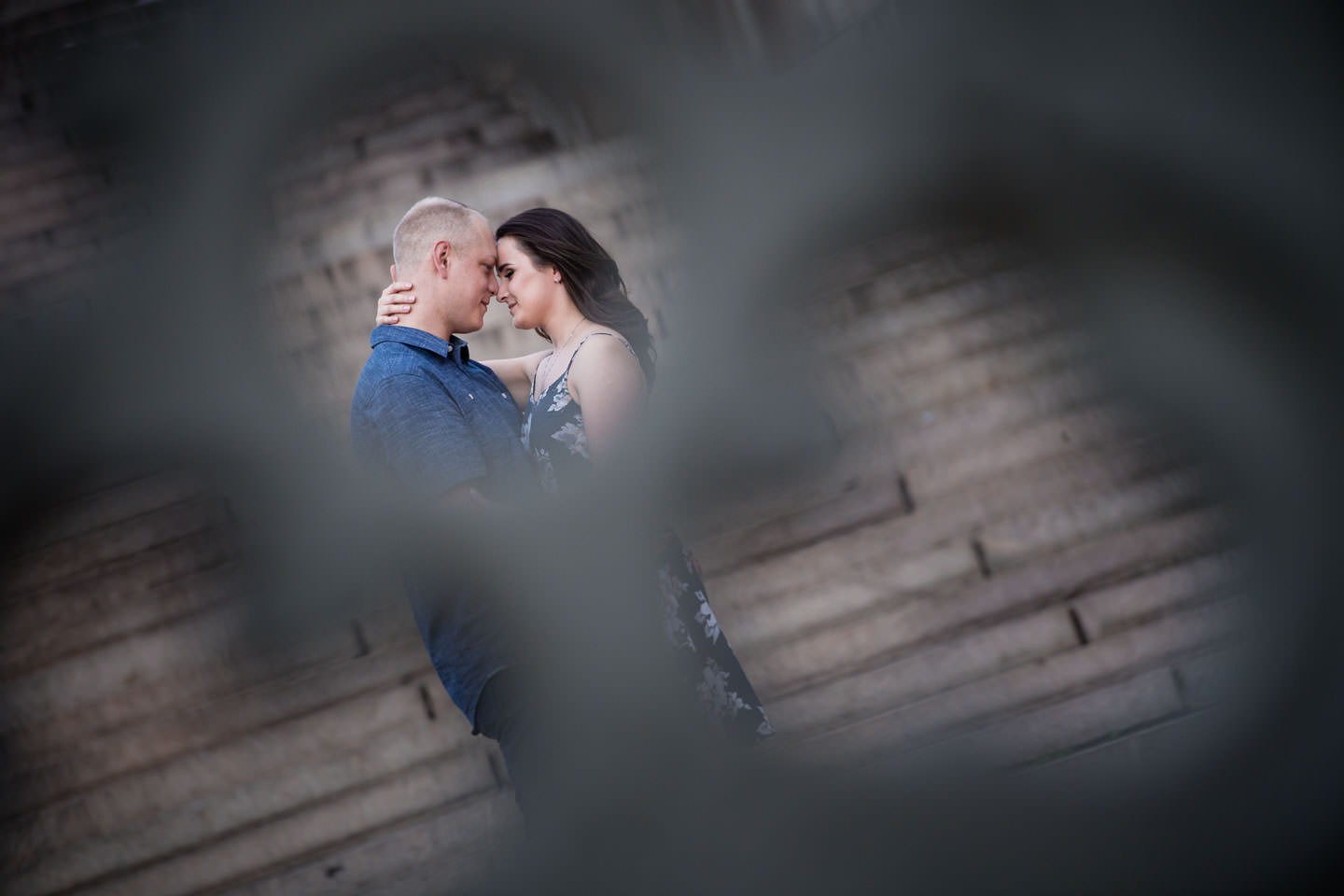 creative pose with couple seen through hold of railing by bethesda terrace and bethesda fountain in central park new york city