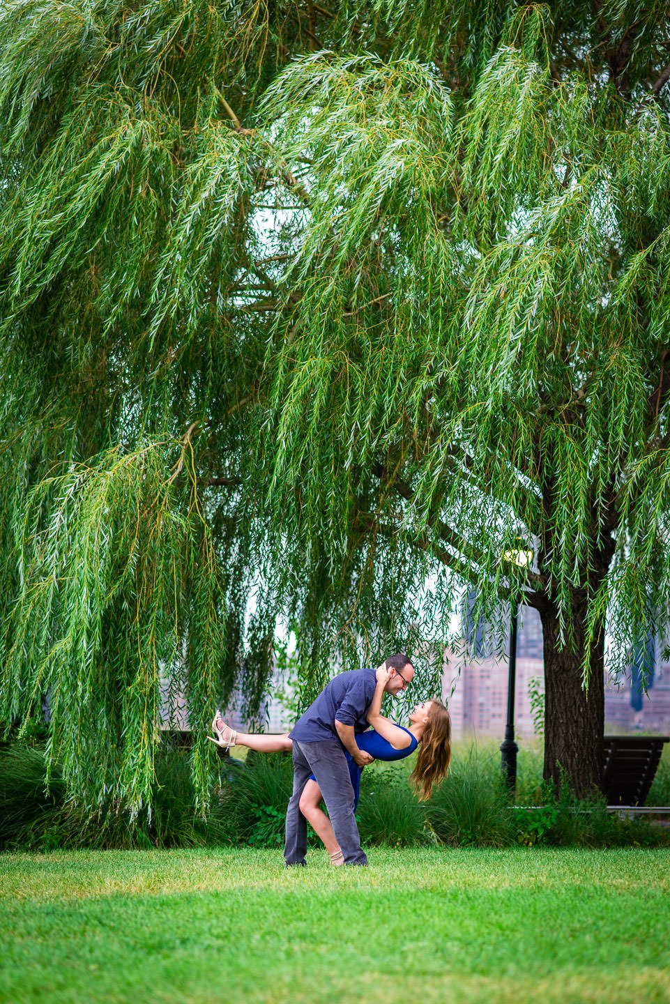couple at gantry plaza state park in long island city new york for engagement session with willow trees doing dip pose
