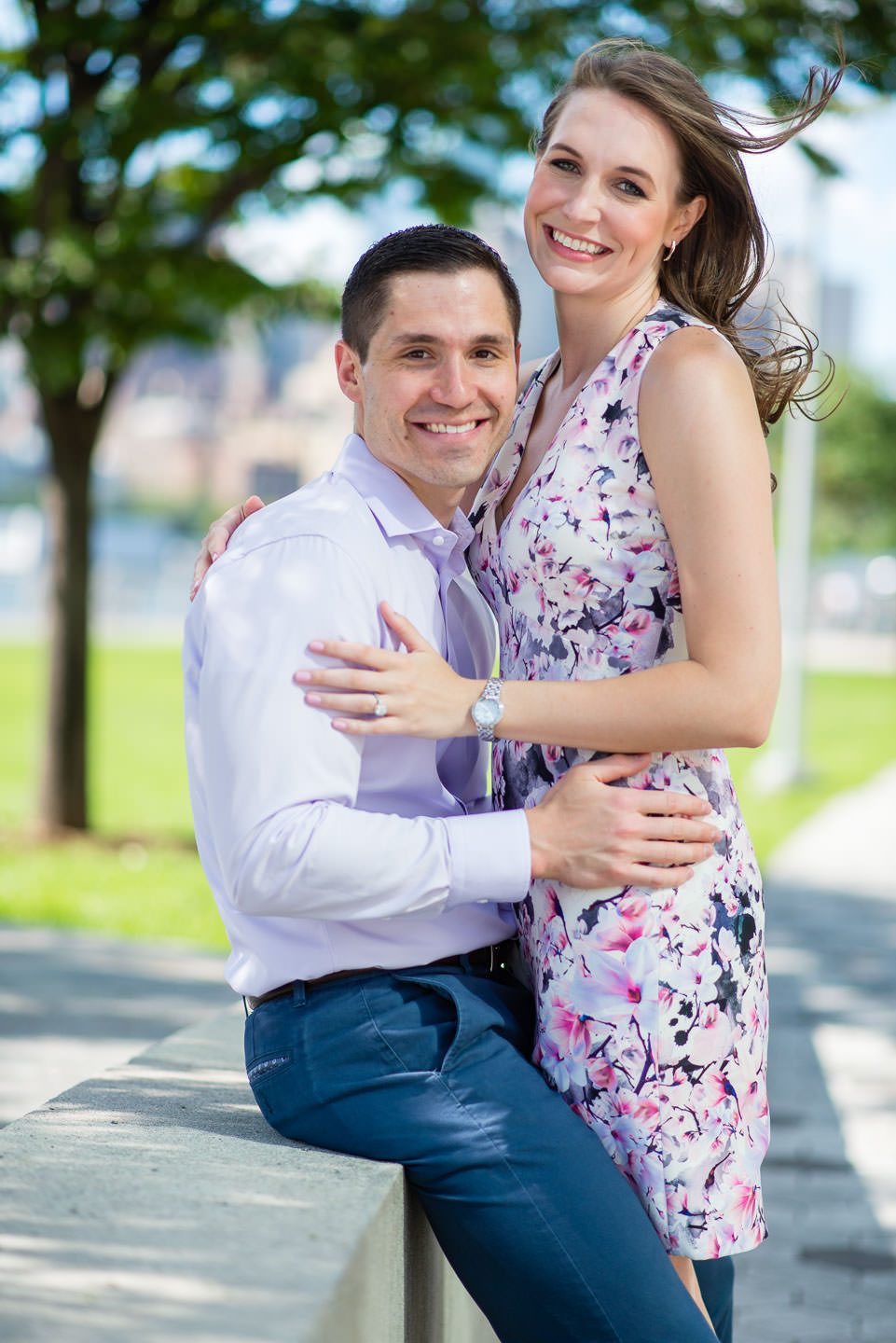 couple in gantry plaza state park for their engagement session in long island city new york looking at camera smiling