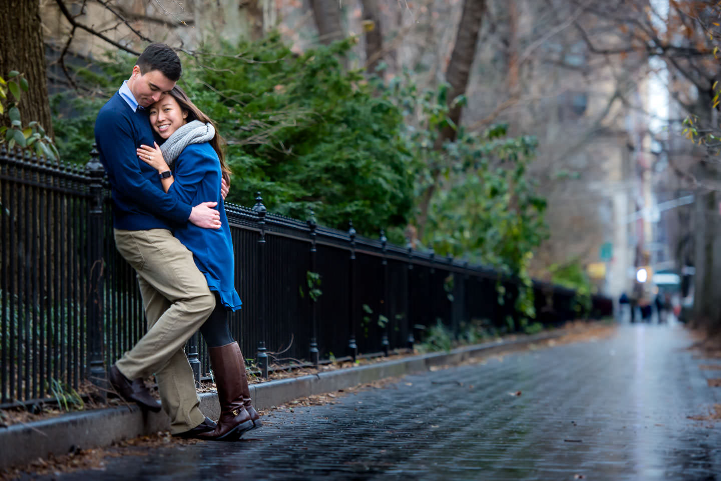 couple on the street with green trees in winter by washington square park in new york city after proposal