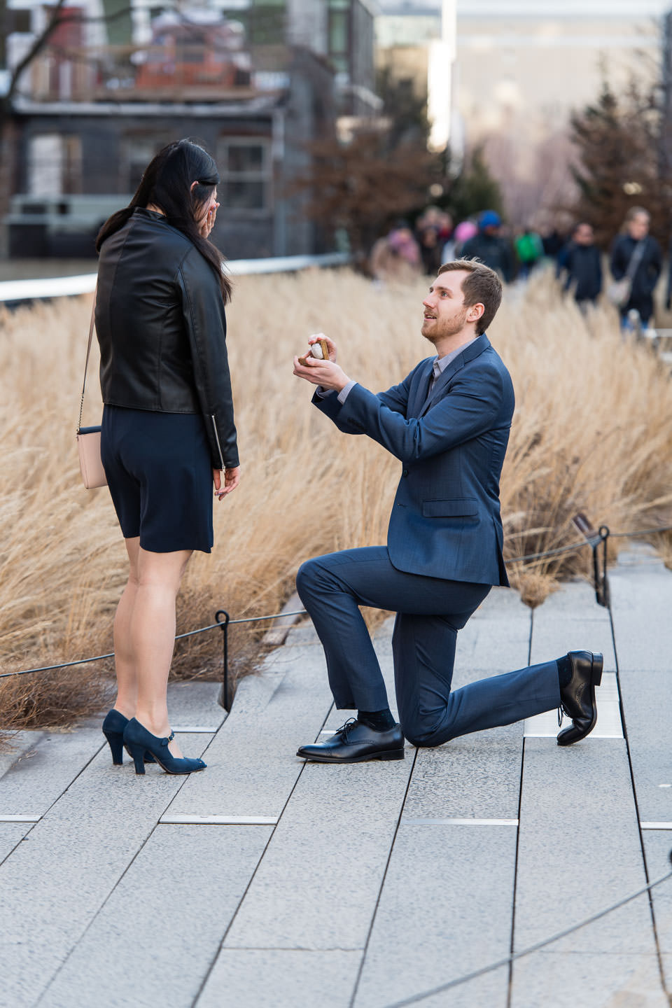 guy proposing on one knee in highline park in new york city