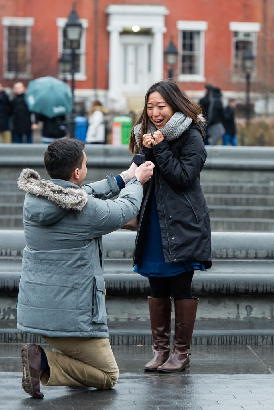 girl very happy as guy is proposing to her in washington square park in winter