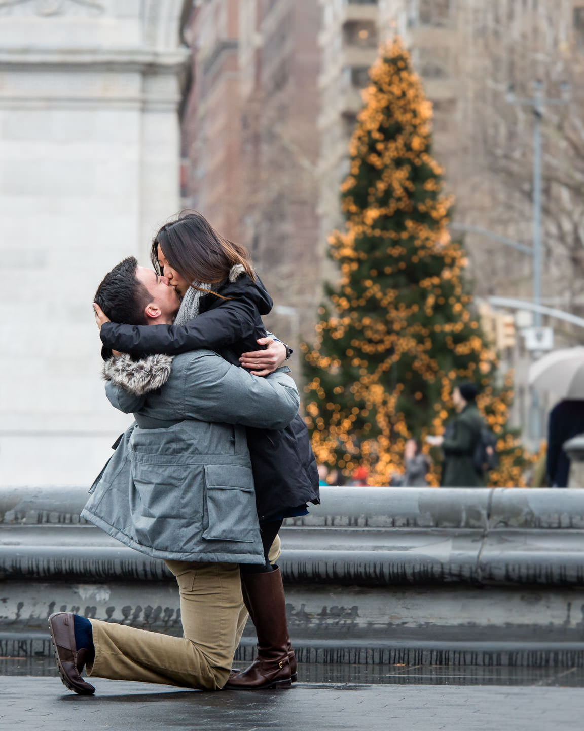 girl very happy as guy is proposing to her in washington square park in winter with christmas tree in background in new york city