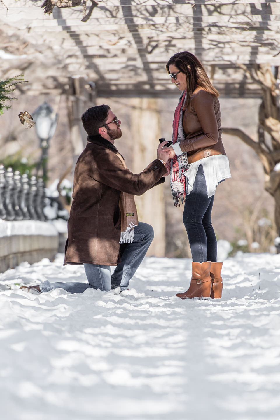 winter proposal in central park with snow guy is on one knee asking for marriage