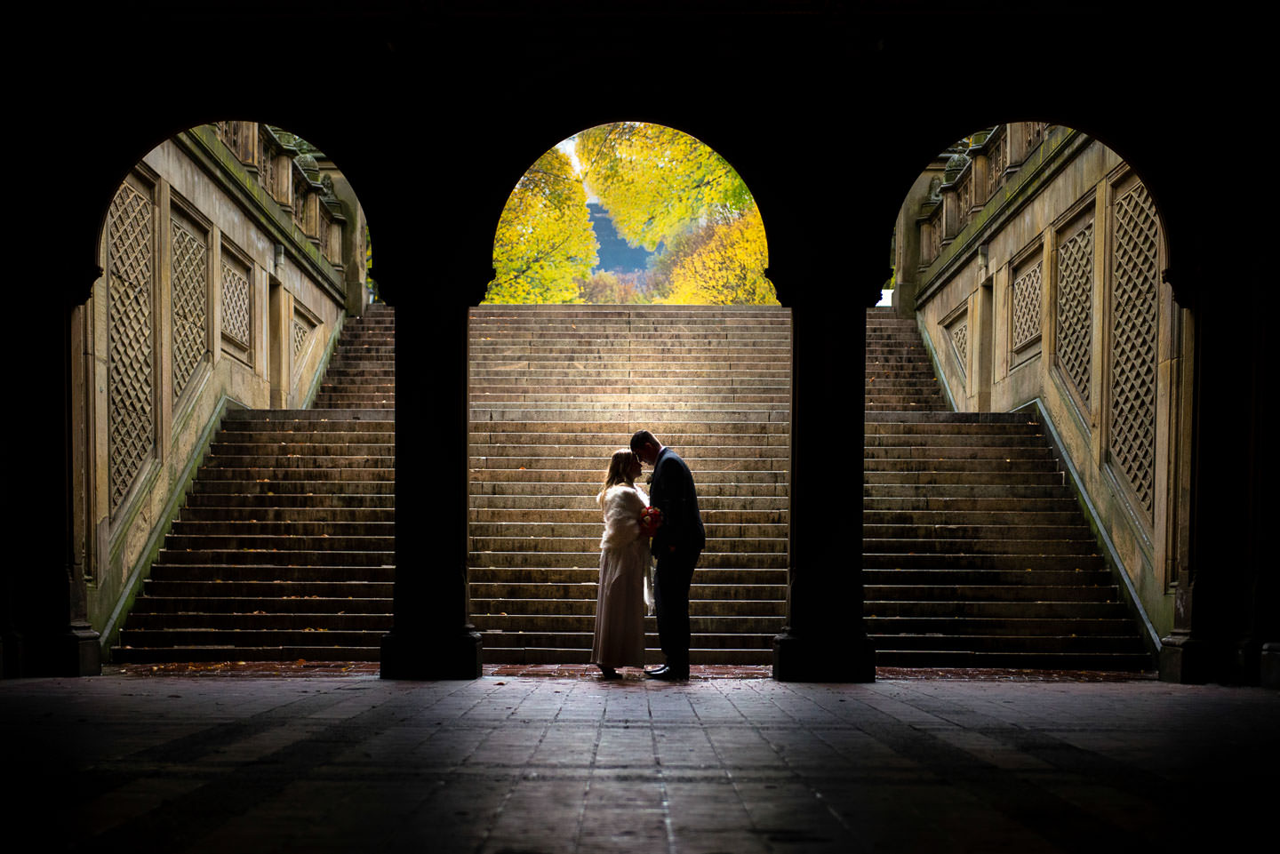 bride and groom under bethesda terrace in central park in the fall artistic photo