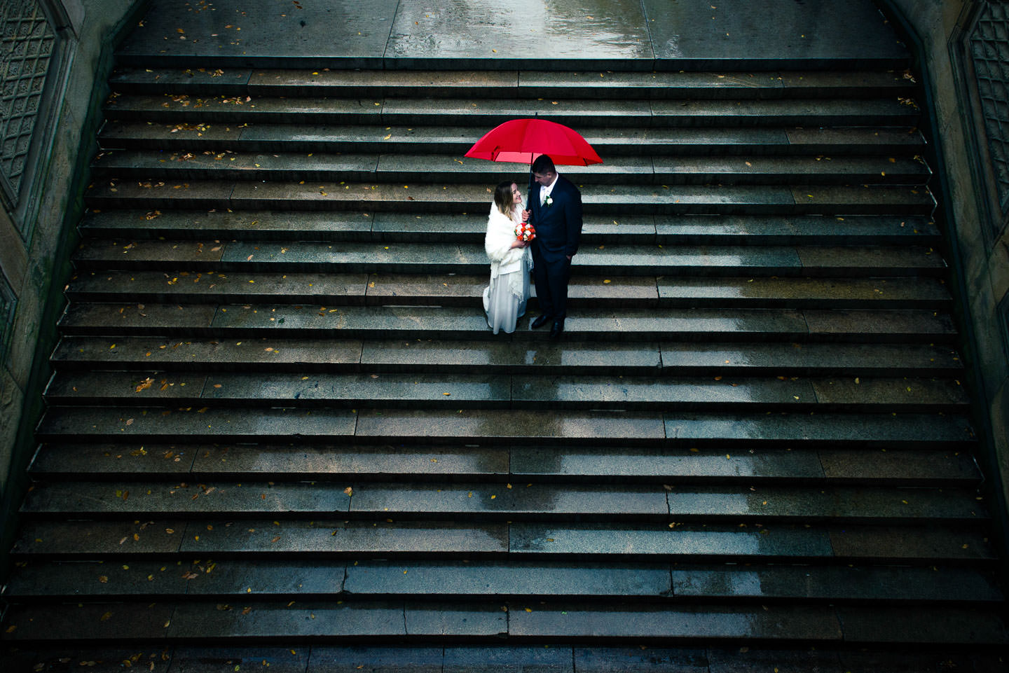 creative photo of bride and groom with red umbrella on bethesda terrace in central park new york city