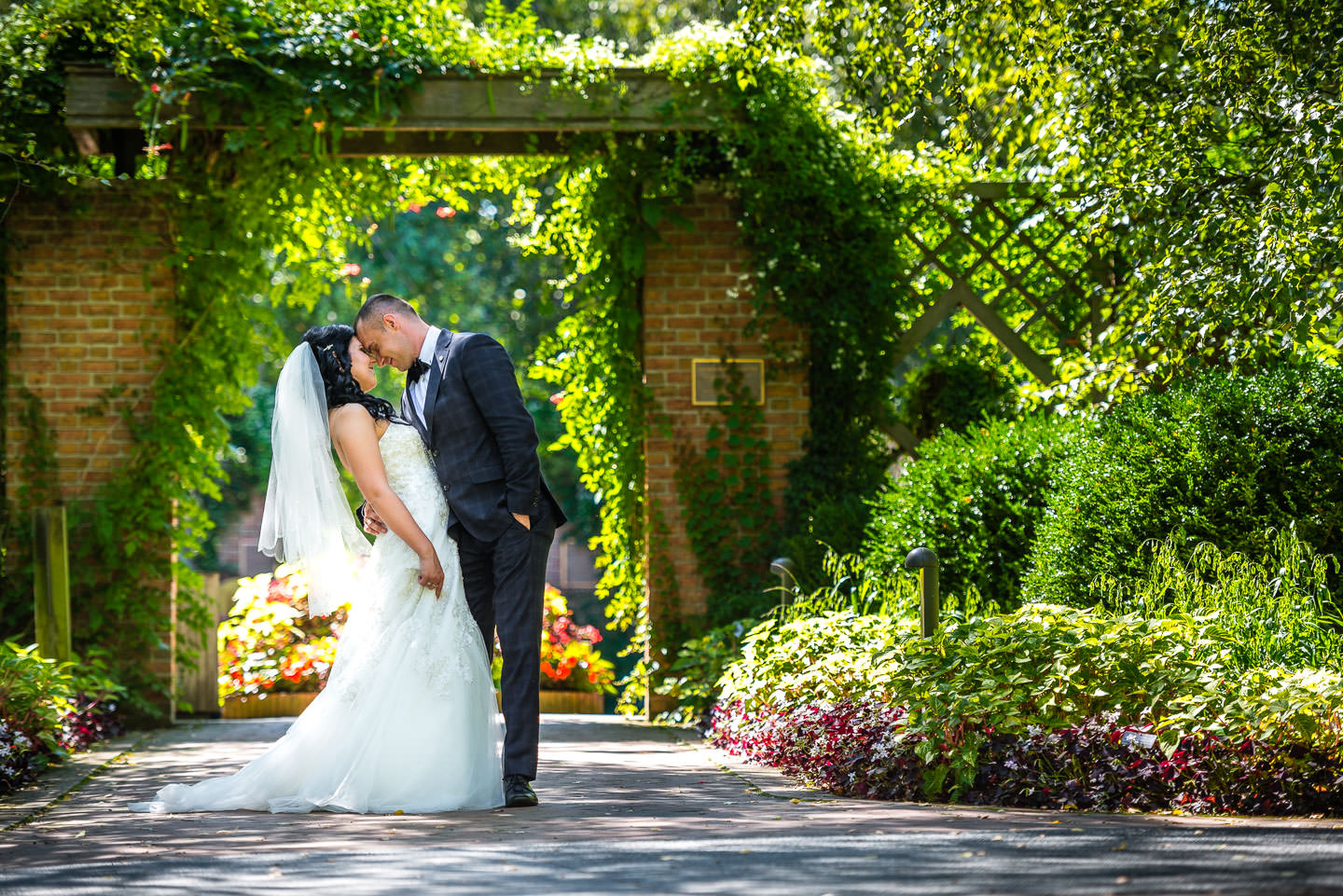 bride and groom in botanical gardens in summer with flowers and trees
