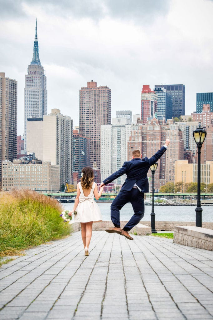 happy groom jumping in gantry plaza state park long island city new york city with empire state building in background holding hands with bride