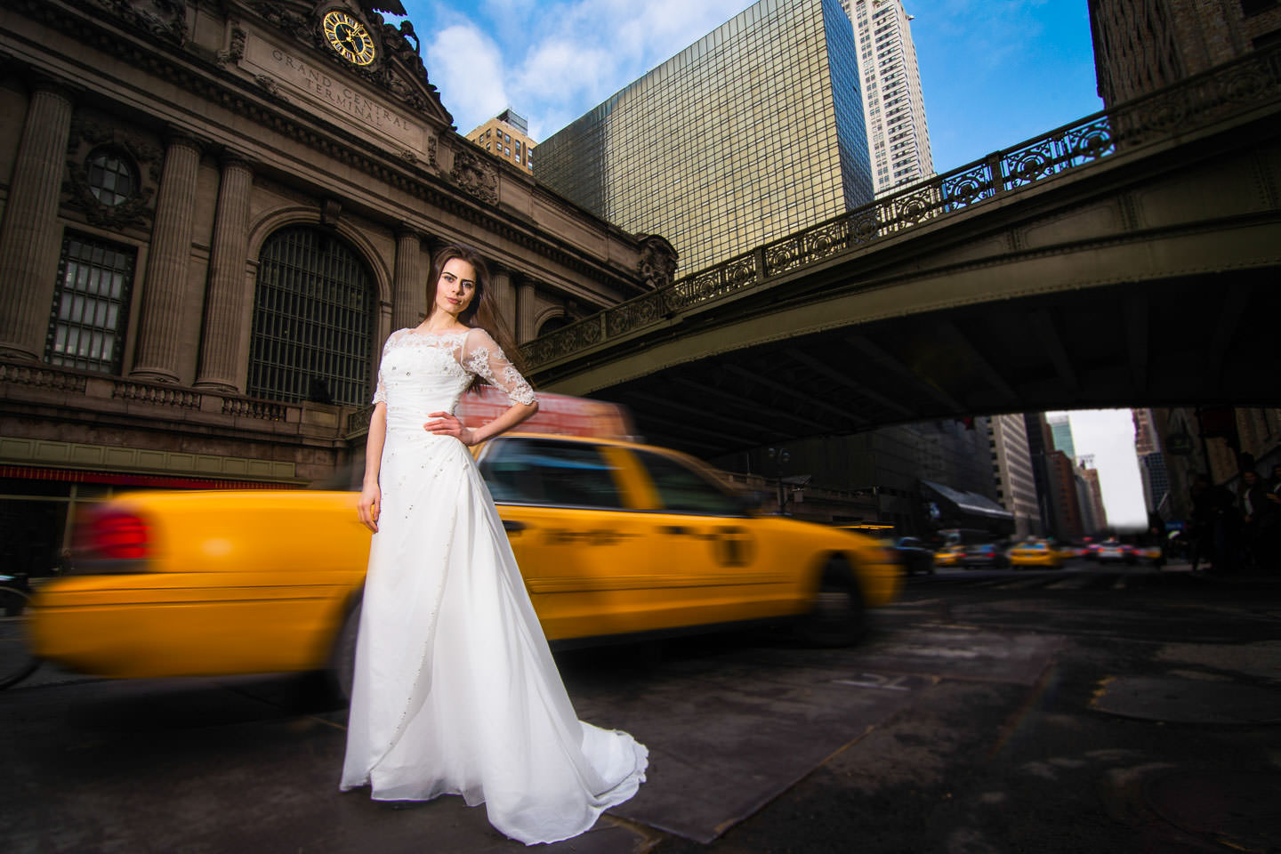 bride in front of yellow taxi by grand central station luxury high end wedding gown davids bridal