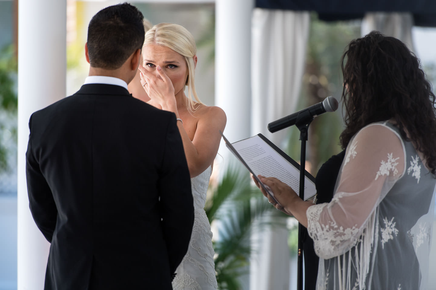 bride crying over groom's shoulder at wedding ceremony in Chateau Briand Caterers long island new york luxury high end wedding